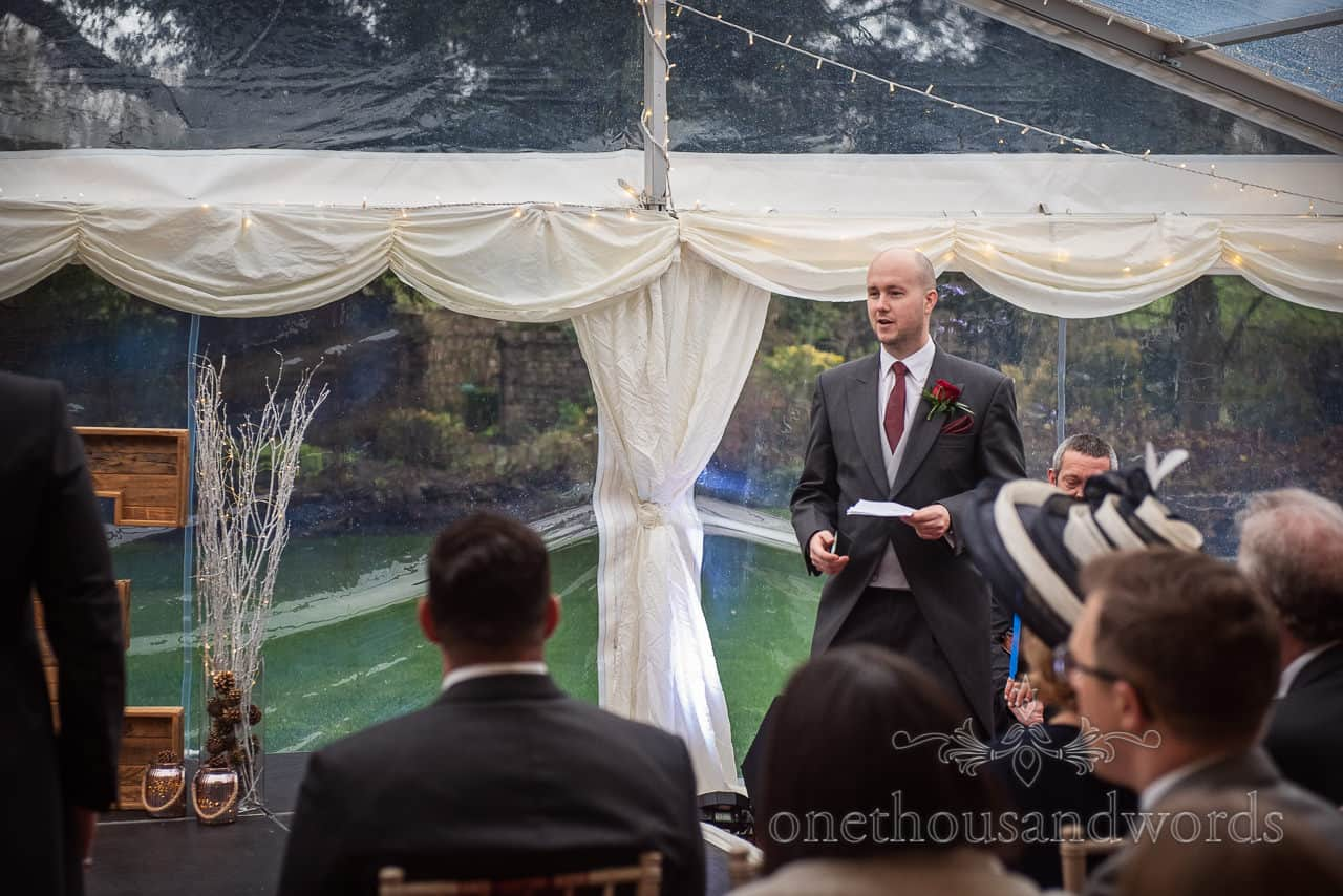Groomsman delivers reading during Smedmore House marquee wedding ceremony