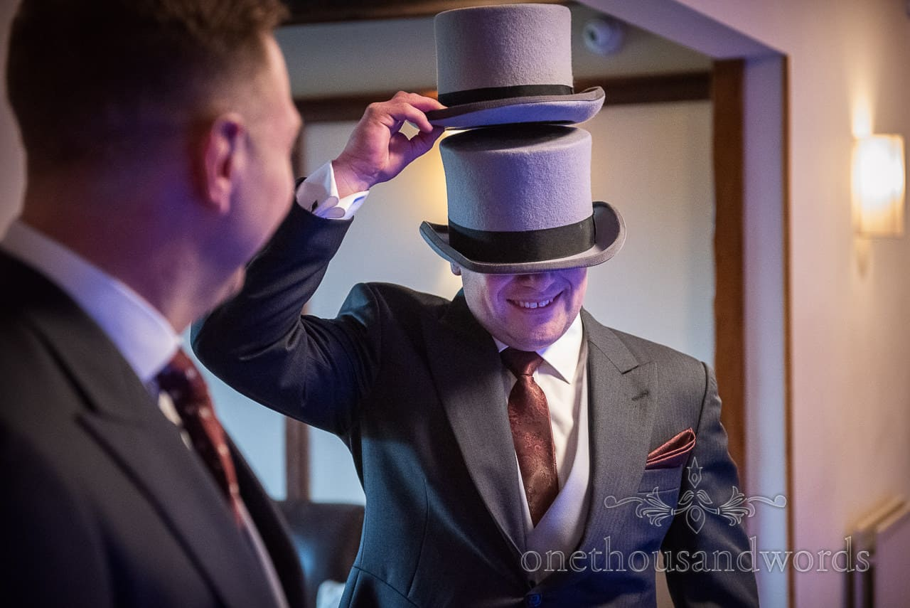 Groomsman fools with top hats before country house wedding