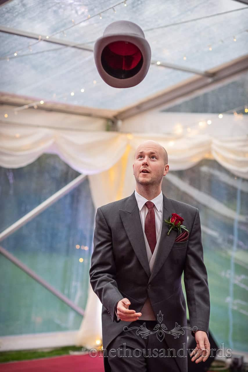 Groomsman tries land top hat on head at Smedmore House wedding