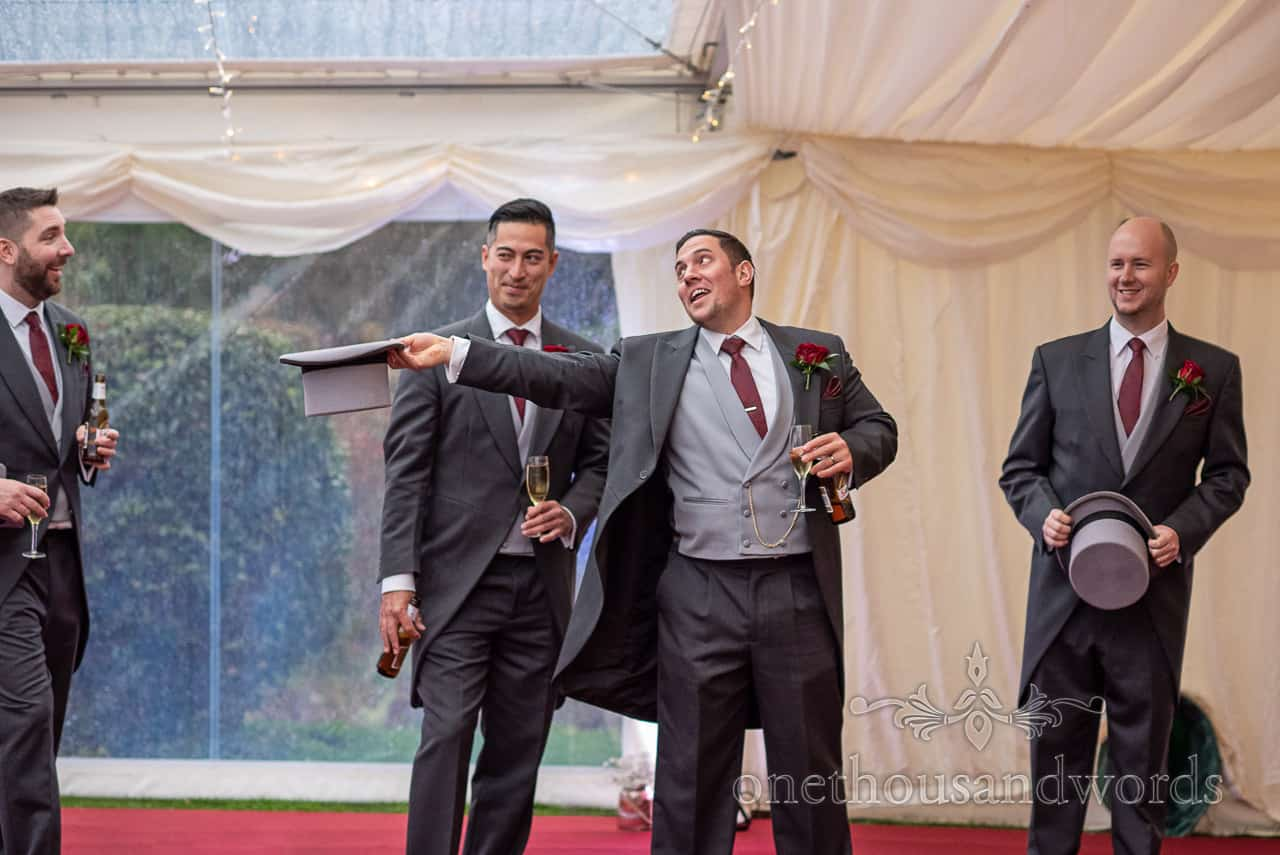 Groomsmen joking around during group photographs at marquee reception