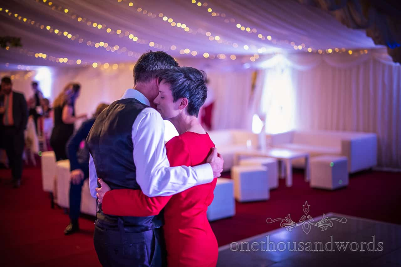 Guests embrace during Smedmore House marquee wedding reception