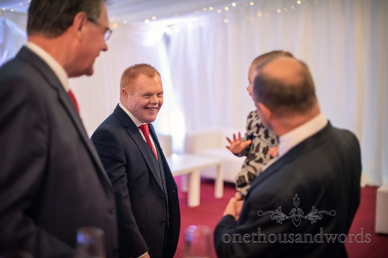 Happy wedding guests in navy suit and red tie at marquee wedding reception photo by one thousand words documentary wedding photography