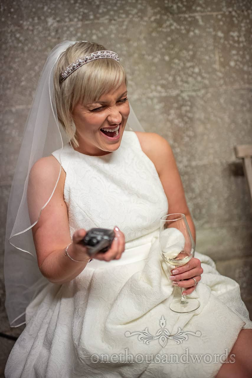 Laughing bride with walkie talkie during country house wedding reception