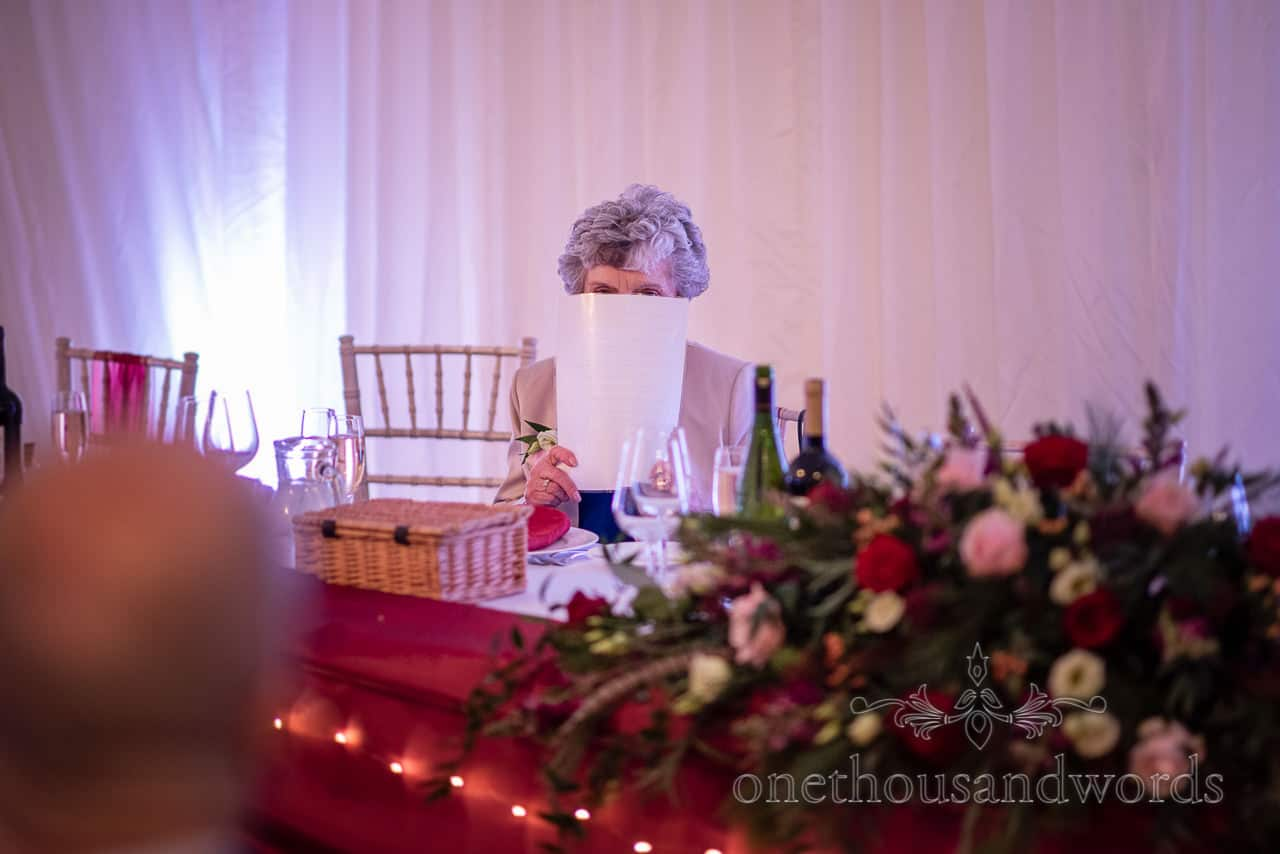 Mother of the bride hides from photographer at marquee wedding reception