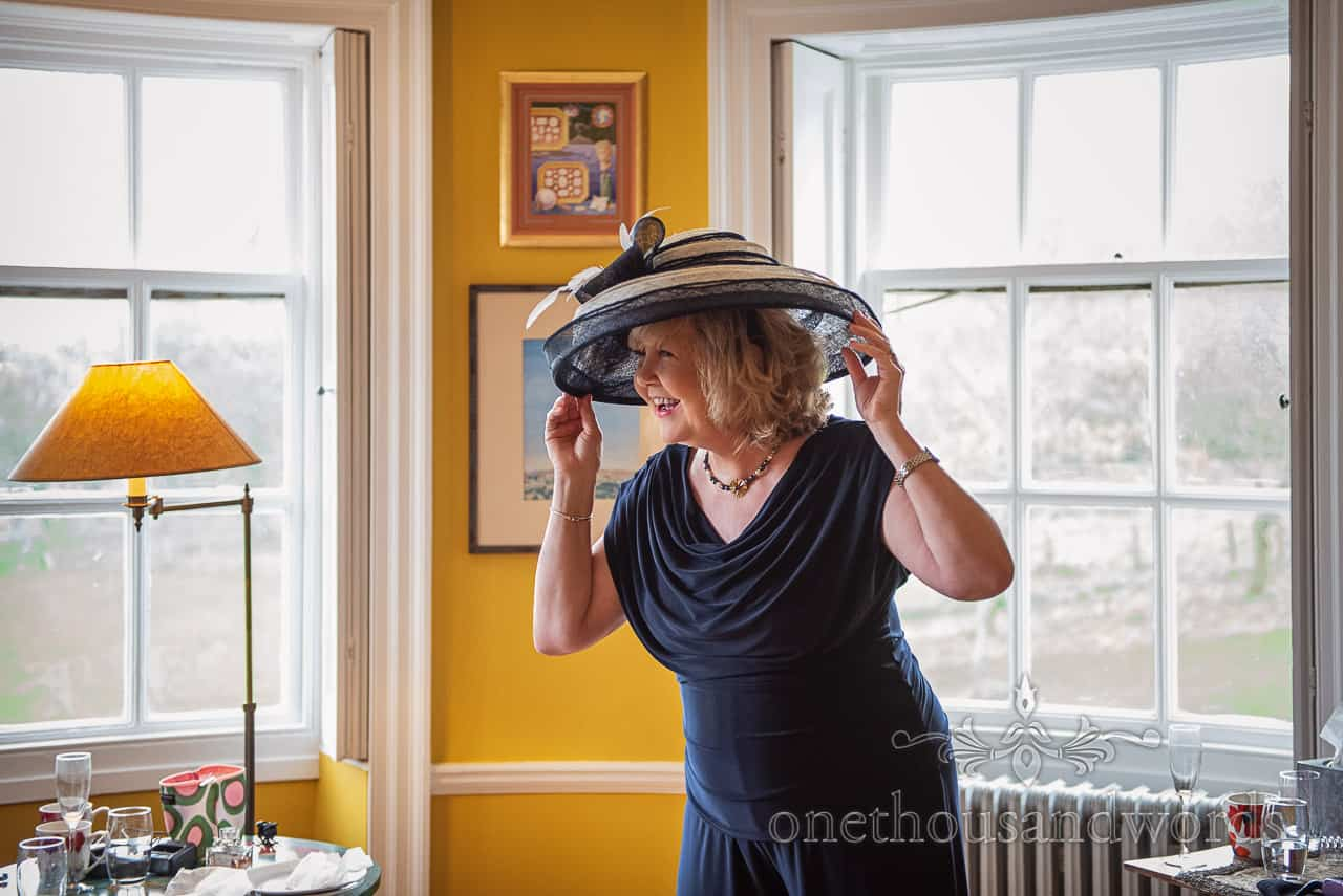 Mother of groom with hat before country house wedding