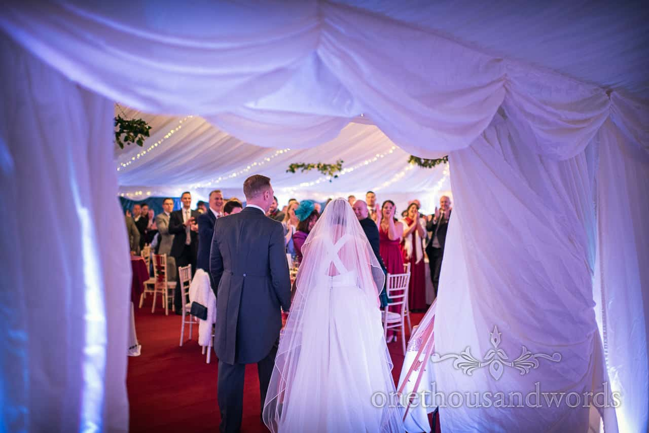 Newlyweds enter marquee at county house wedding reception