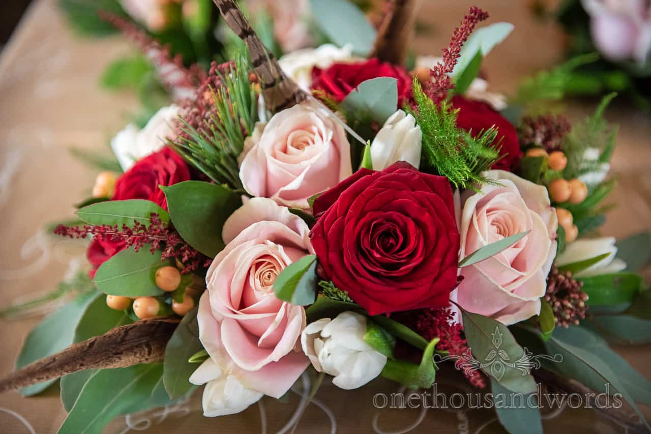 Red and pink roses sat among green and red foliage and game bird feathers in bridal bouquet photograph by one thousand words photography