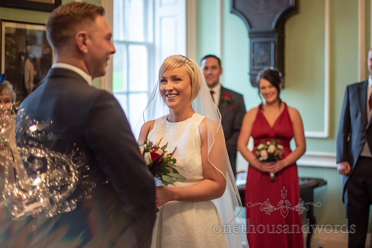 Smedmore House Dorset country house indoor wedding civil ceremony photograph with chandelier reflection and laughing wedding party