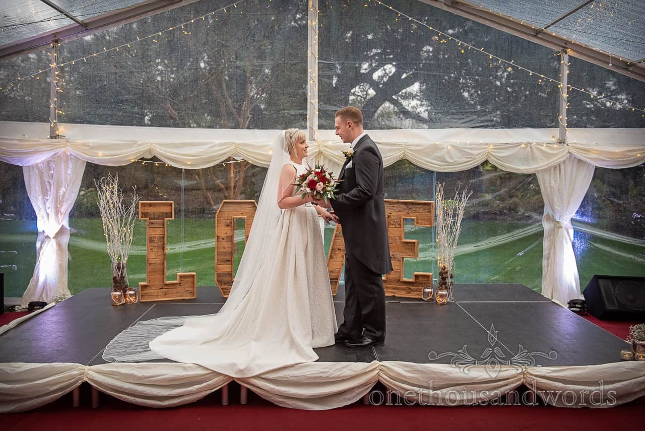 Smedmore House wedding photographs of bride and groom on marquee stage with giant wooden love letters by one thousand words photography