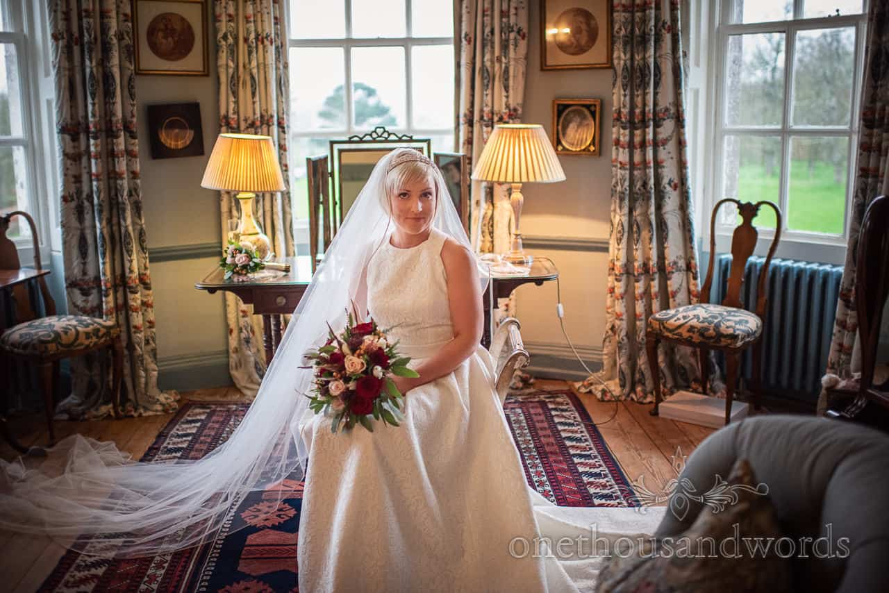 Smedmore House wedding photographs of bride wedding ready in white dress and veil sitting in bridal preparation room by one thousand words