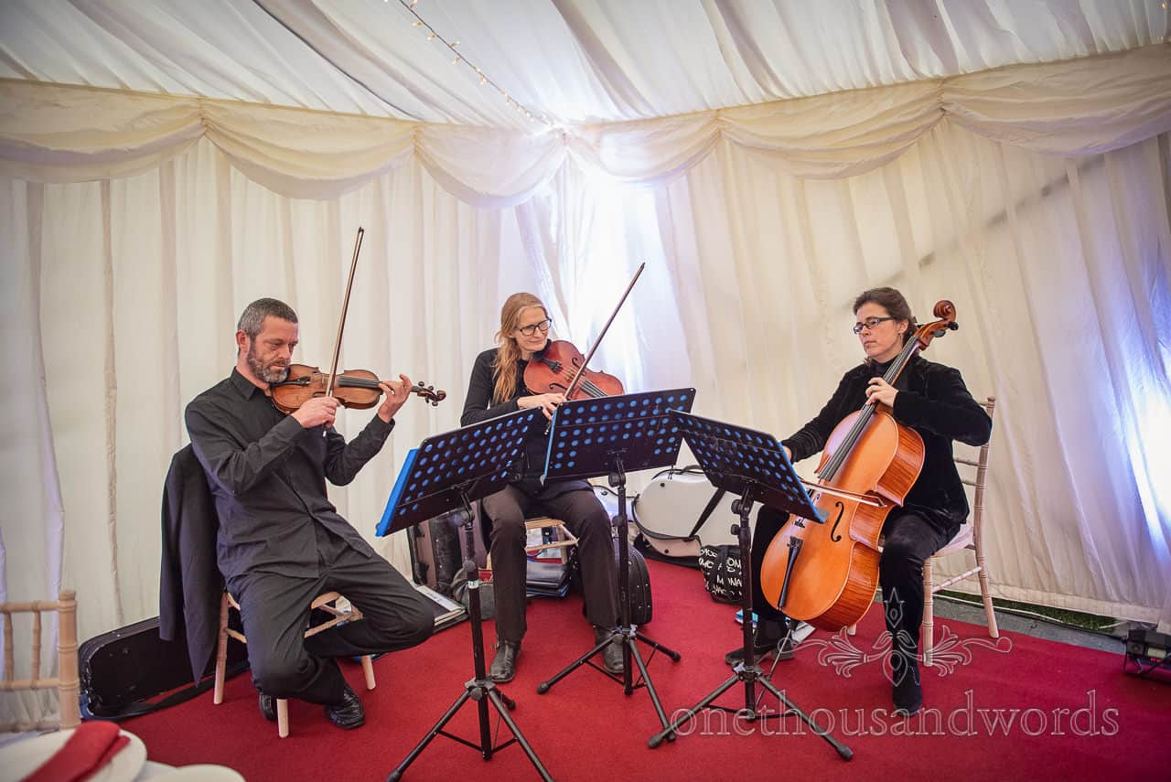 Documentary wedding photograph of string trio playing music in wedding marquee drinks reception with red carpet