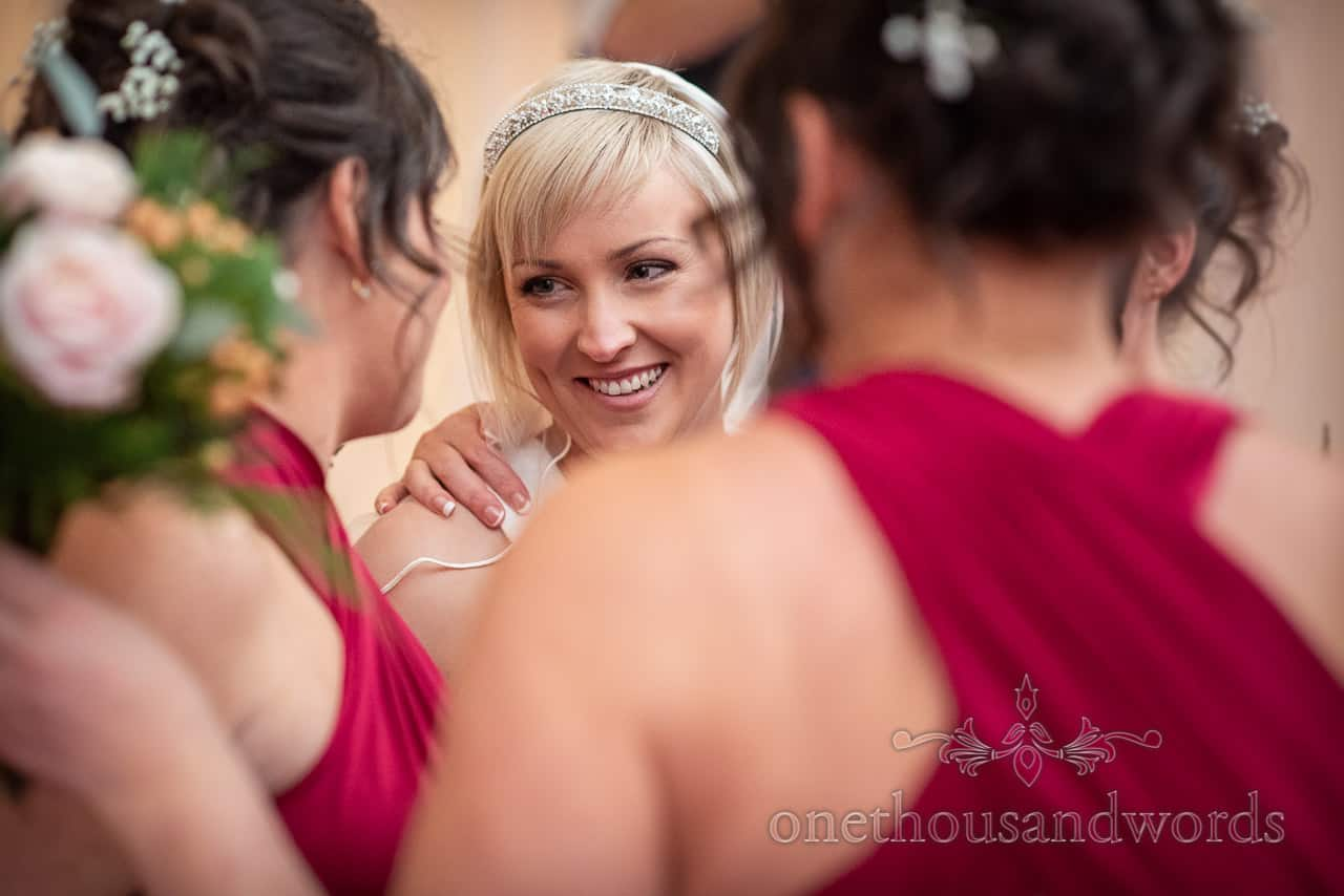 Happy bride portrait photograph surrounded by bridesmaids in red dresses at drinks reception by one thousand words documentary photographers