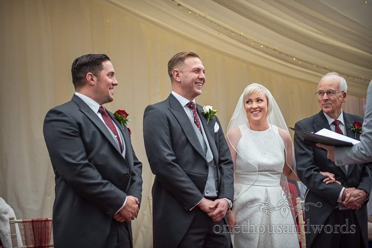 Documentary photograph of Bride and groom laughing at each other during Smedmore House marquee wedding ceremony in Dorset