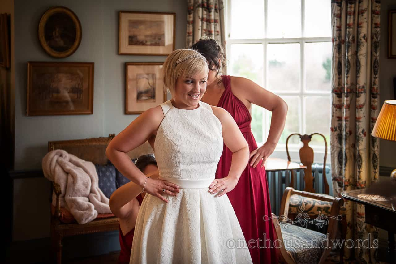 Smiling bride is laced into her classic style wedding dress at Smedmore House Dorset countryside wedding venue
