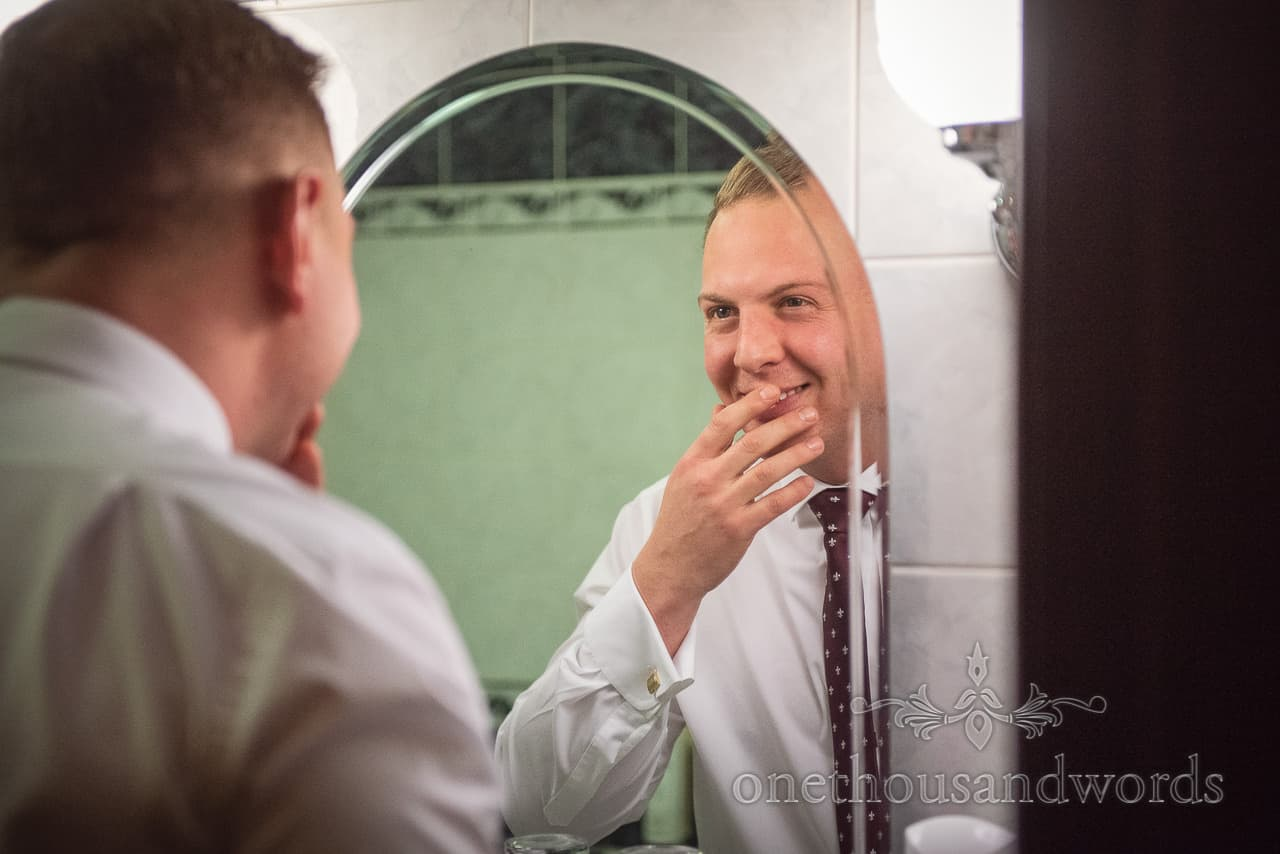 Groom smiles at himself in a hotel bathroom mirror during wedding morning preparation photographs by one thousand words photography