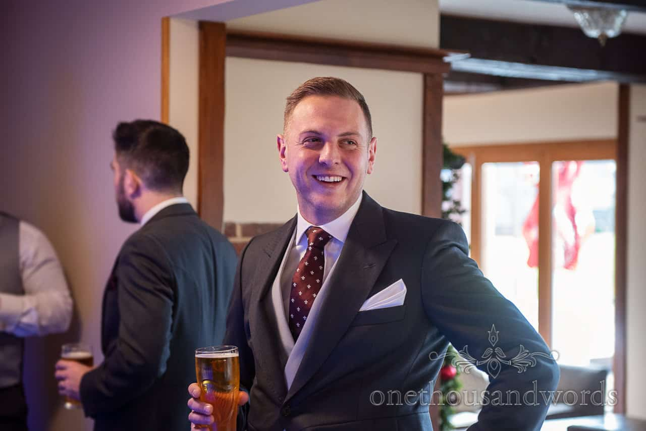 Documentary wedding photograph of smart groom smiling on wedding morning with a pint of beer in the hotel bar