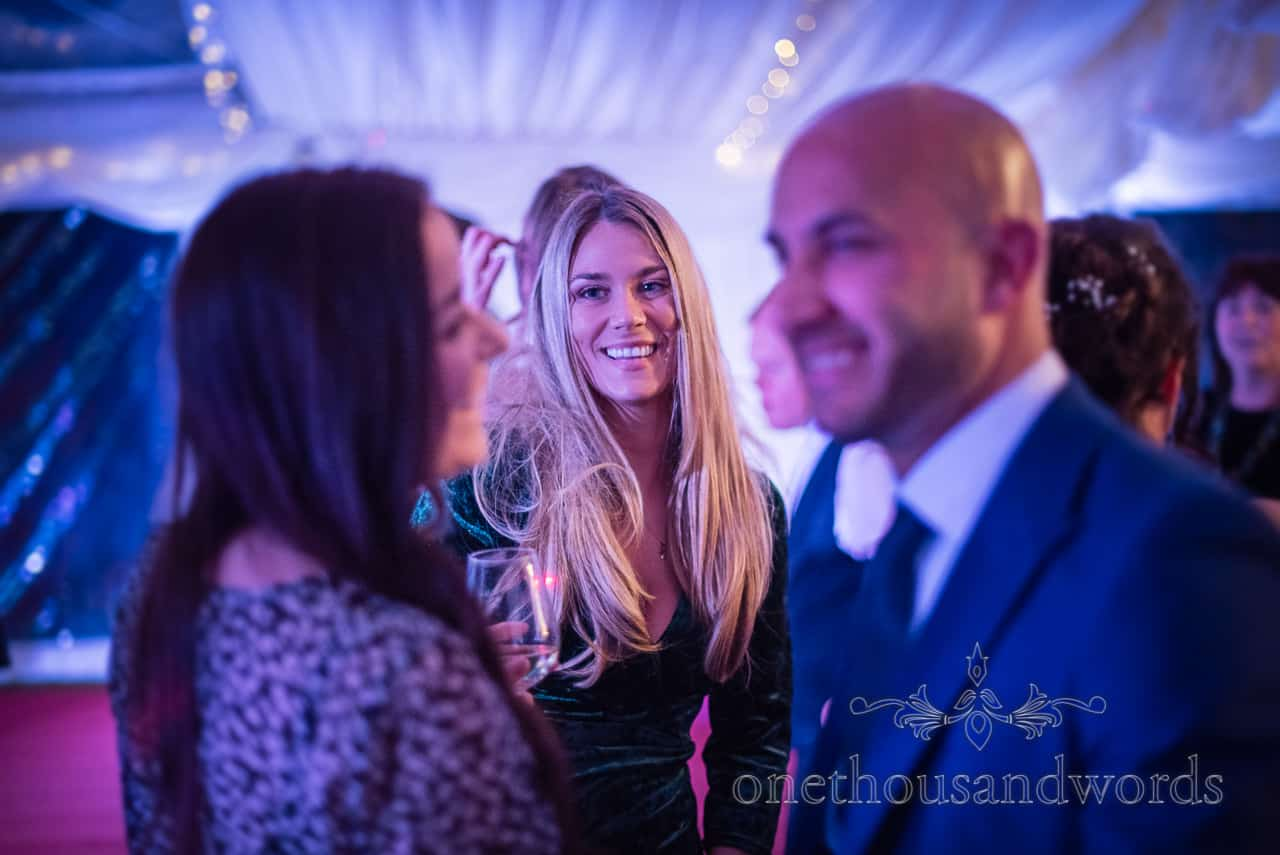 Documentary wedding photograph of happy smiling blonde wedding guest dancing under blue disco lights in wedding marquee