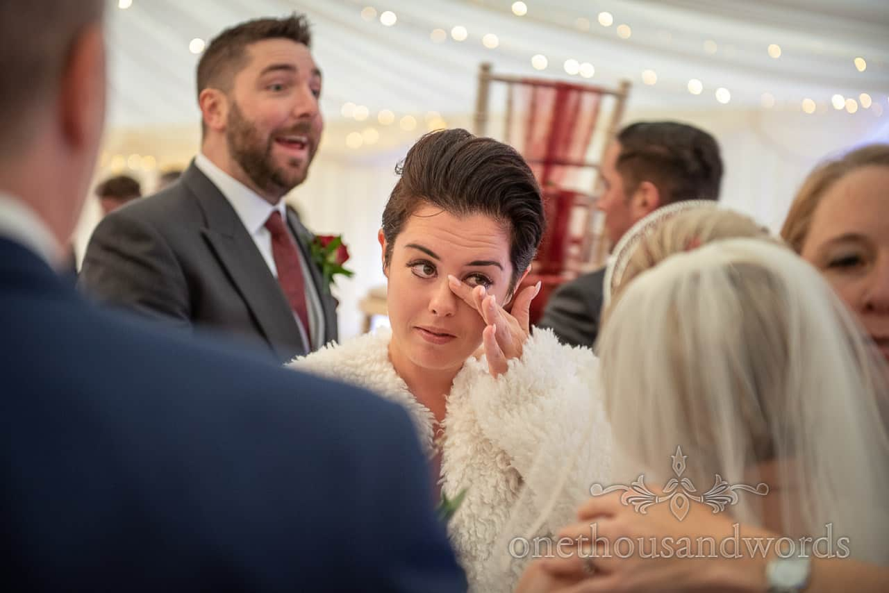 Emotional moment photographed as tearful female wedding guest wipes away the tears at wedding marquee drinks reception
