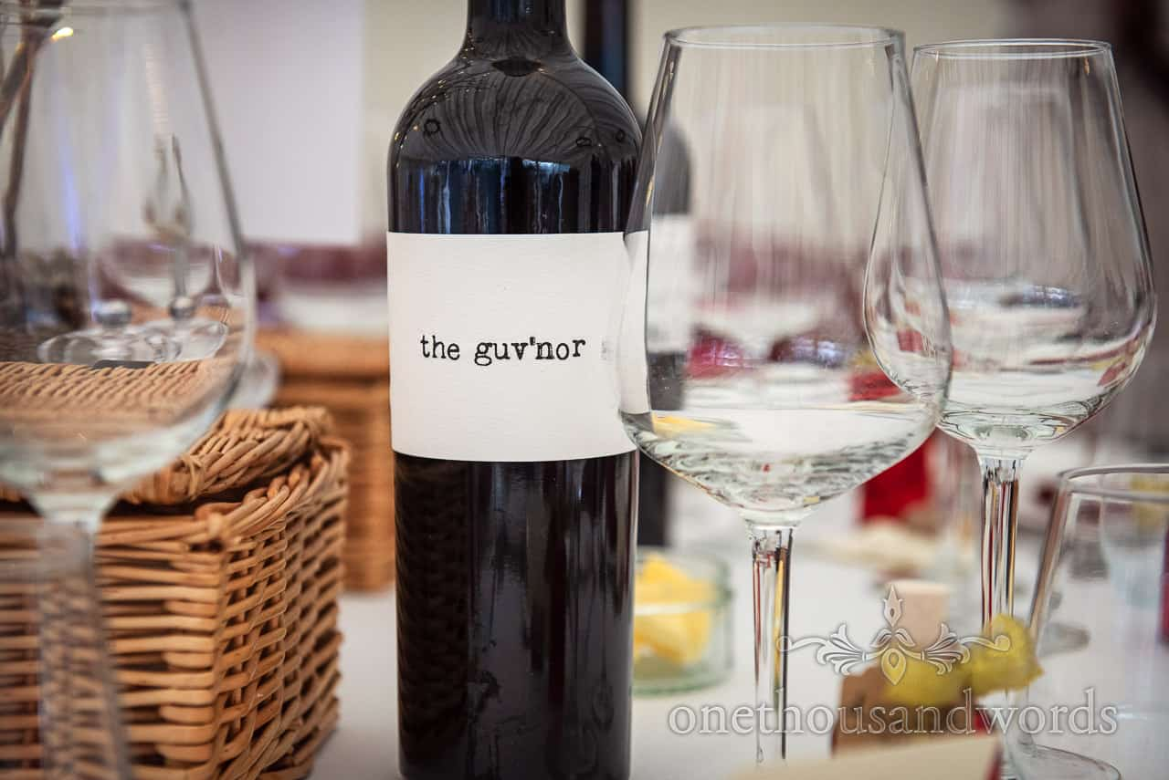 The Guvnor red wine bottle close up detail photograph on wedding breakfast table with wicker hampers and wine glasses