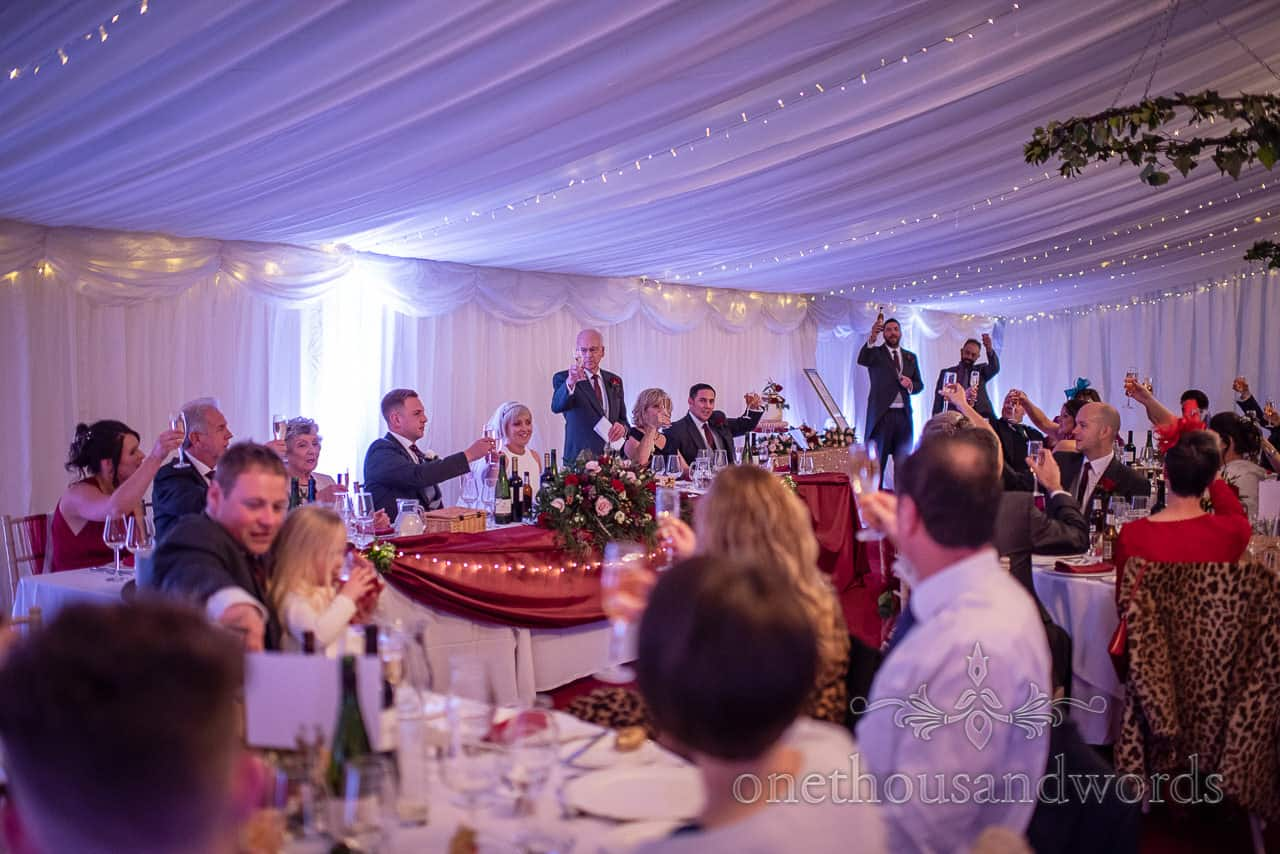 Photograph of father of the bride raising a drinks toast during Smedmore House wedding marquee speeches