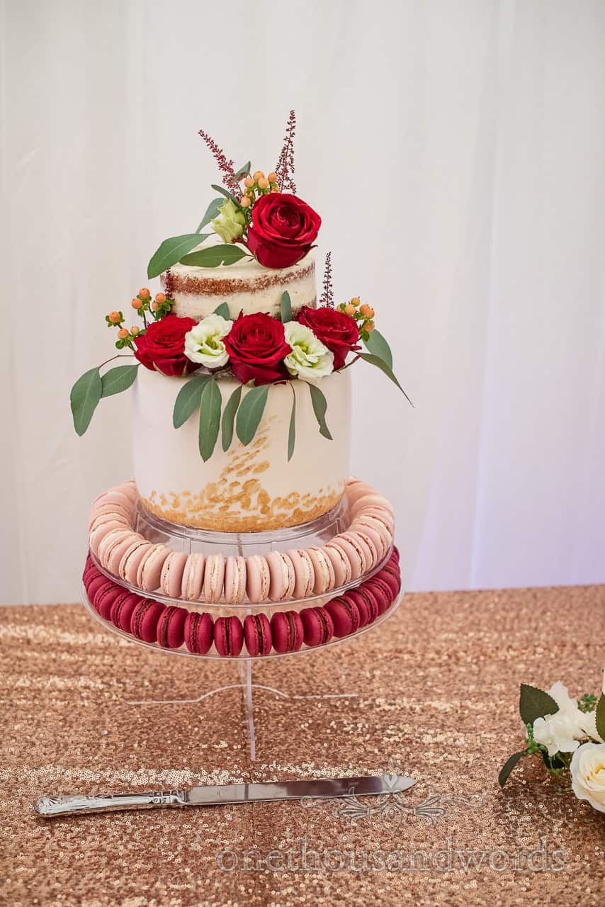 Photograph of two tiered iced naked wedding cake with red roses and red and pink macaroons