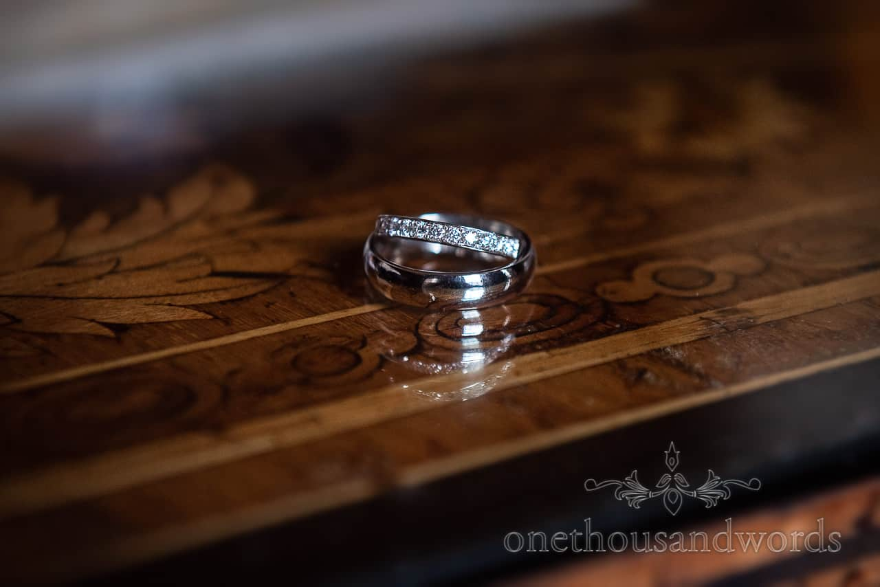Silver and diamond wedding rings with reflection on ornate polished wooden table photograph