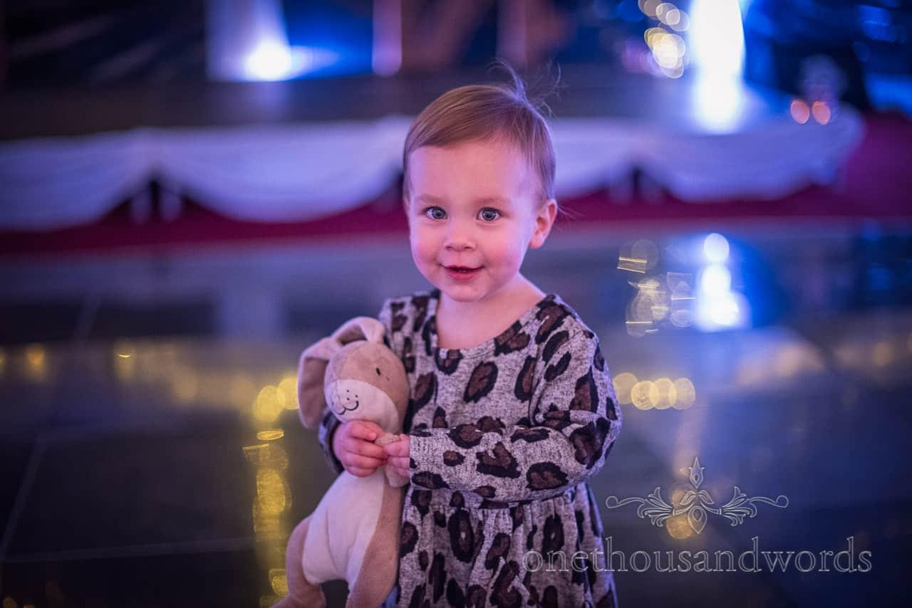 Cute child wedding guest with cuddly toy on wedding dance floor under blue disco lights
