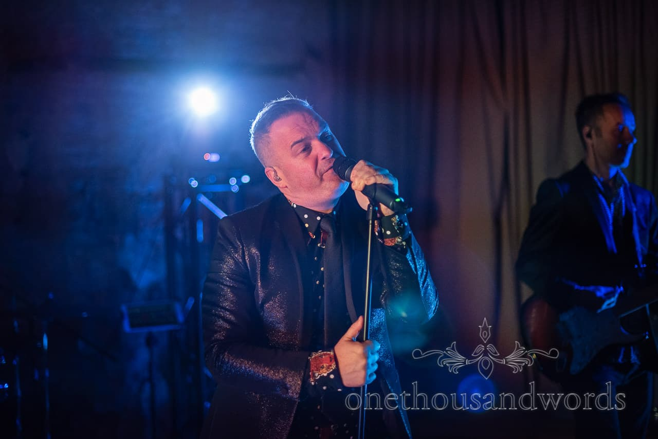 Band front man performs in stage lights at Lulworth castle wedding reception