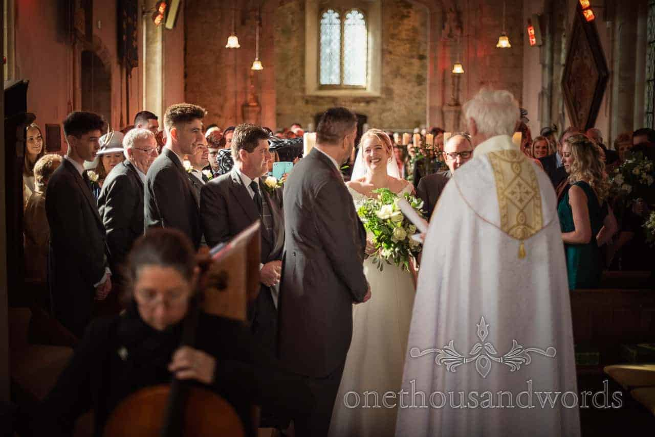 Bride arrives at altar escorted by father during Lulworth Estate wedding photographs