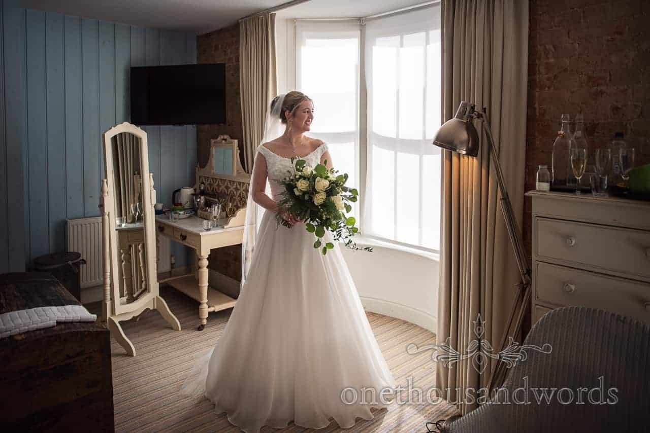 Bride in wedding dress bathed in sunlight coming through window at Lulworth Cove Inn