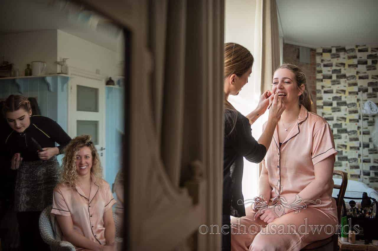 Documentary bridal preparation photograph with bridesmaid reflected in mirror