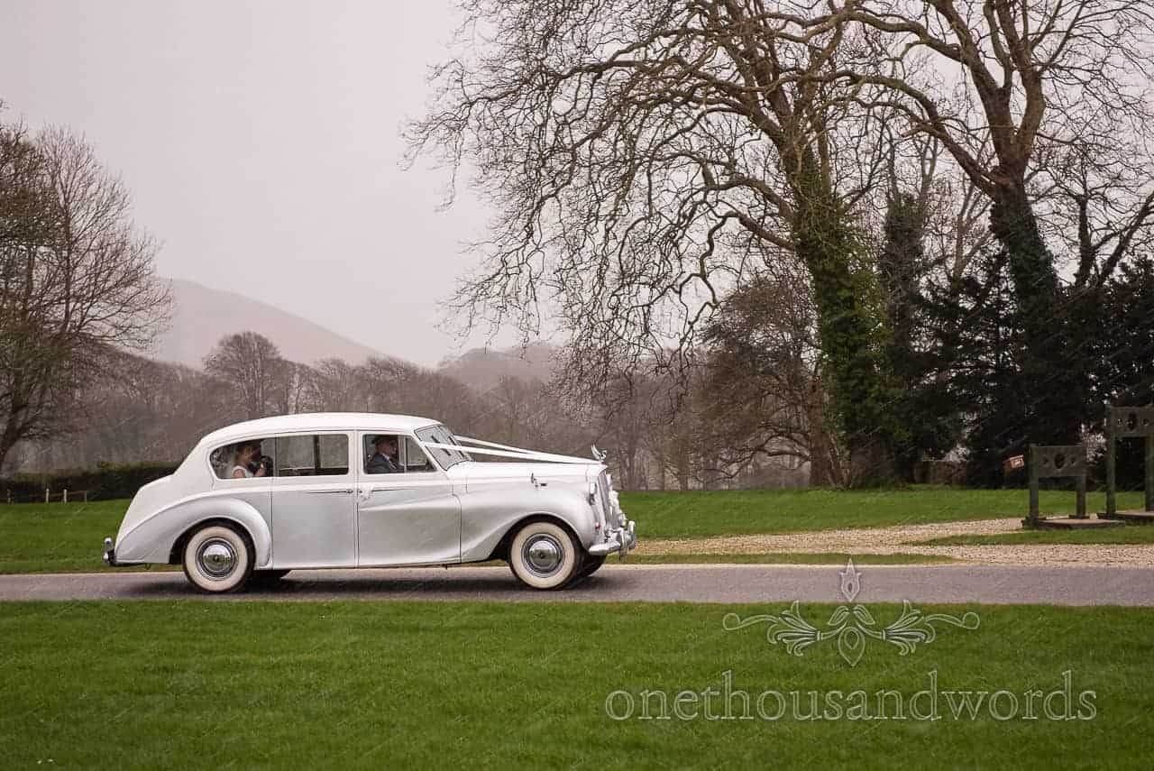 Bride And Groom Travel In Classic Silver Wedding Car On Route In Rain To Lulworth Castle