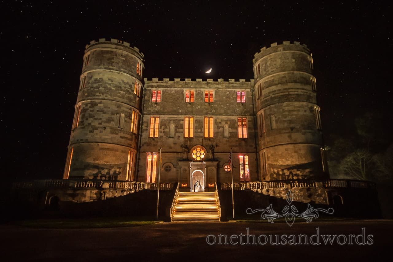Bride and groom outside in doorway at night for Lulworth Castle wedding photographs