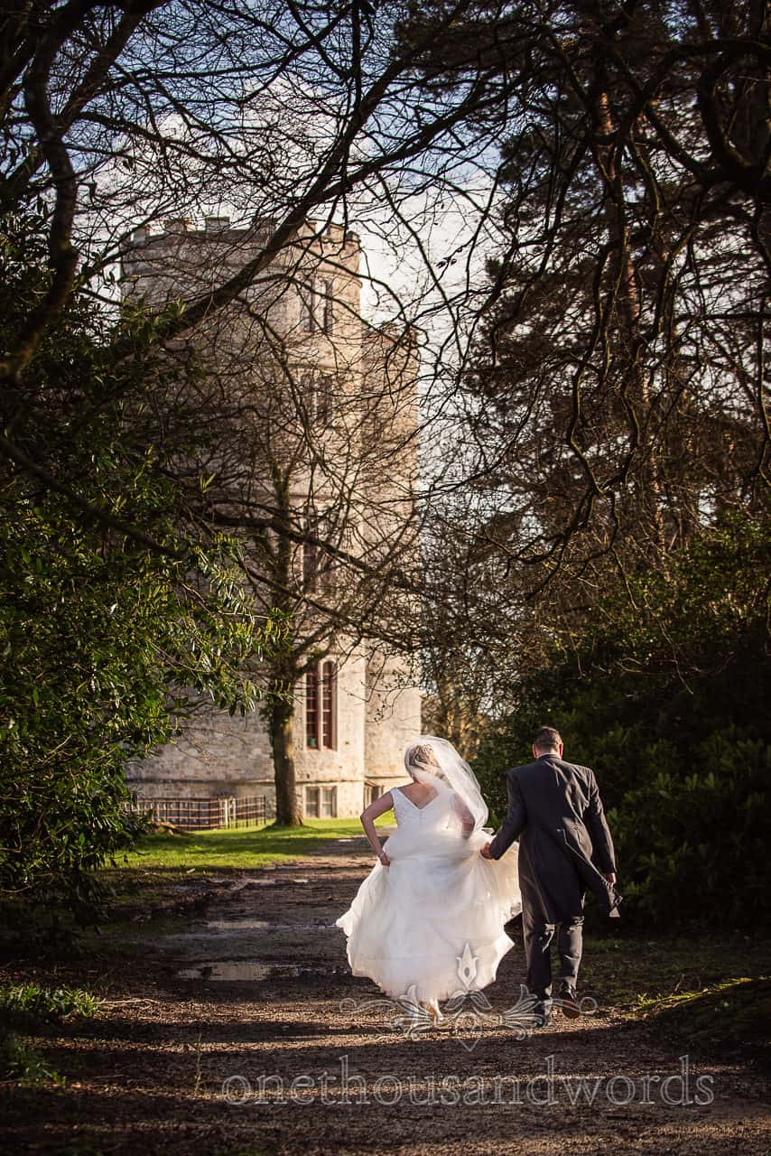 Bride and groom walk back along gravel path towards castle at Lulworth Estate wedding in Dorset