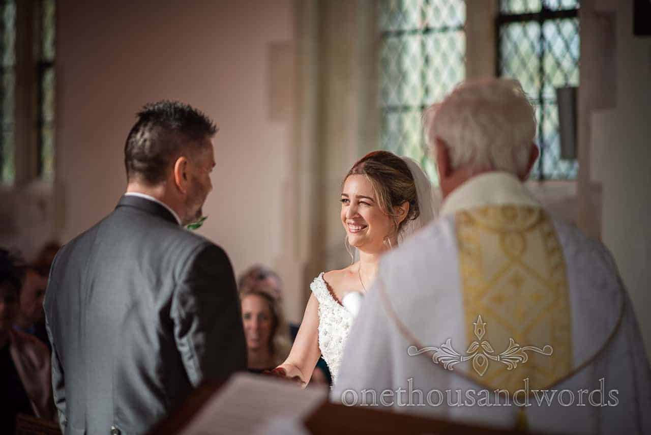 Bride looks at groom during Lulworth Estate church wedding ceremony