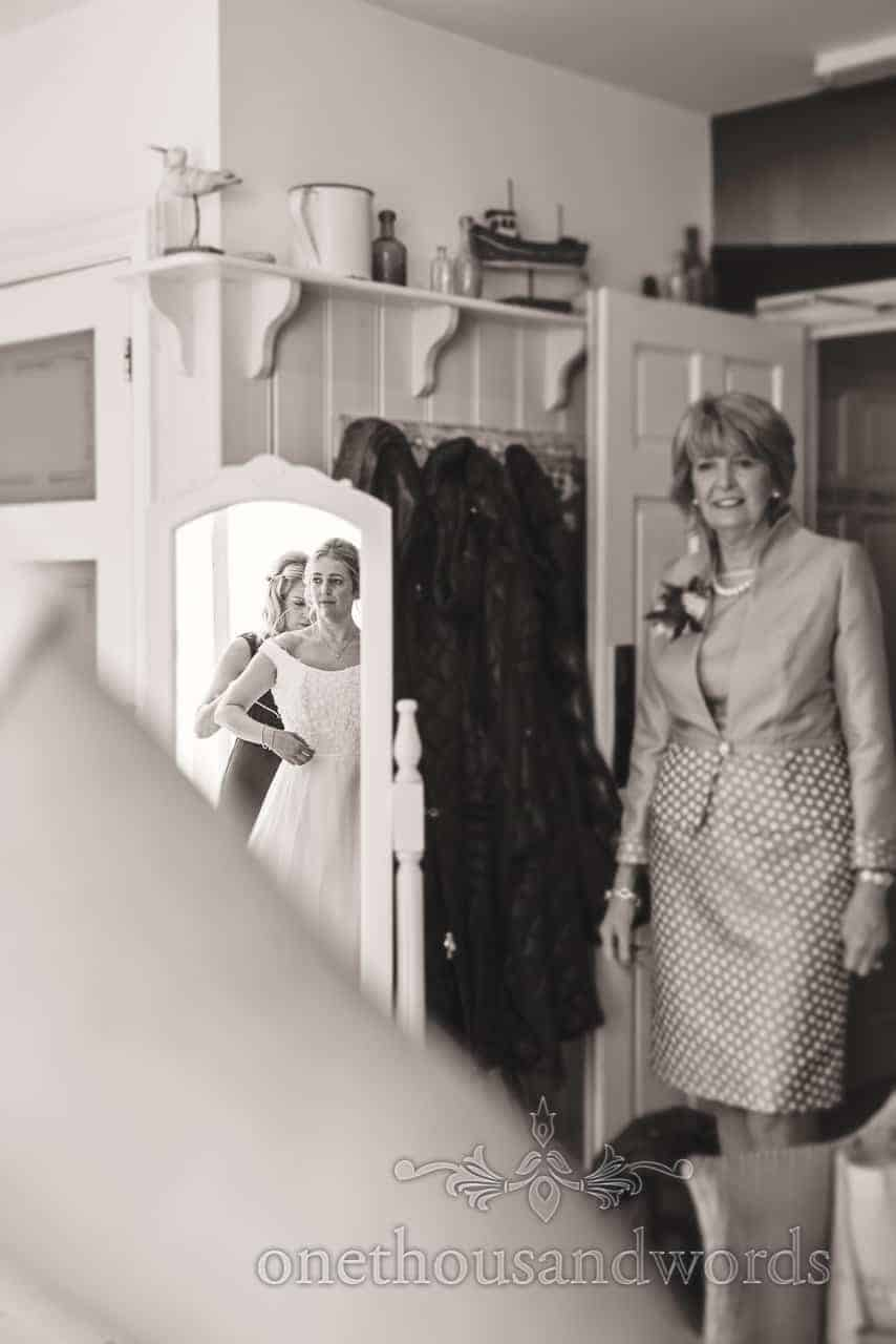 Bride in mirror is aided by bridesmaid while mother looks on during wedding morning