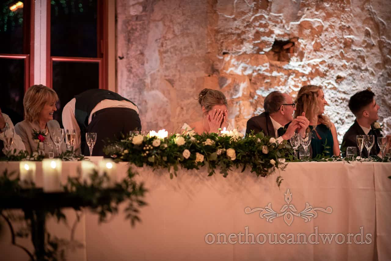 Bride reaction during grooms speech at Lulworth Estate Castle evening wedding reception