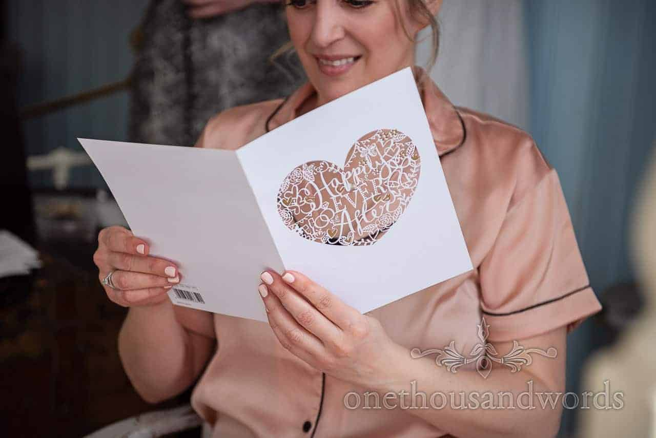 Smiling bride reads etched happily ever after card from husband to be