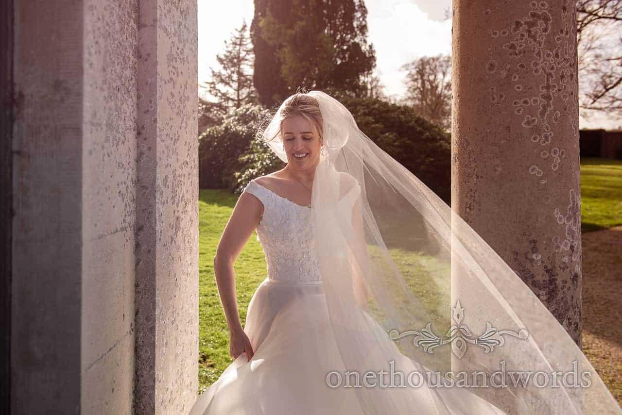 Brides veil blows In wind at Lulworth Estate wedding photographs
