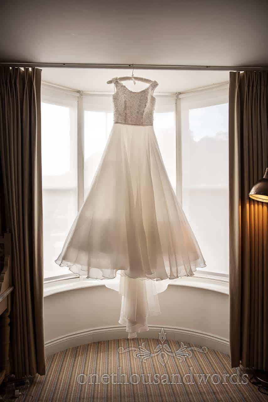 Brides dress hangs in window Lulworth Cove Inn on wedding morning
