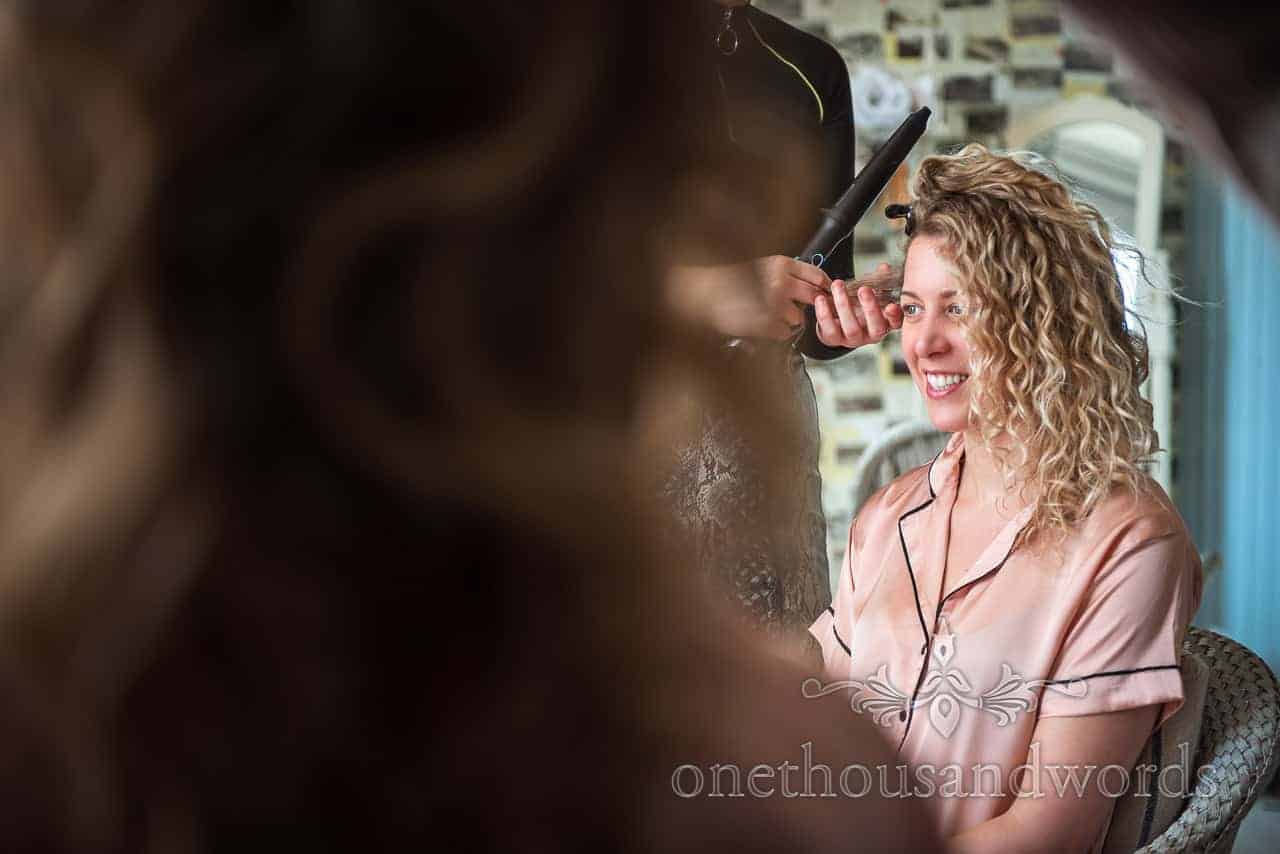 Documentary photo of bridesmaid hair styling during bridal preparations