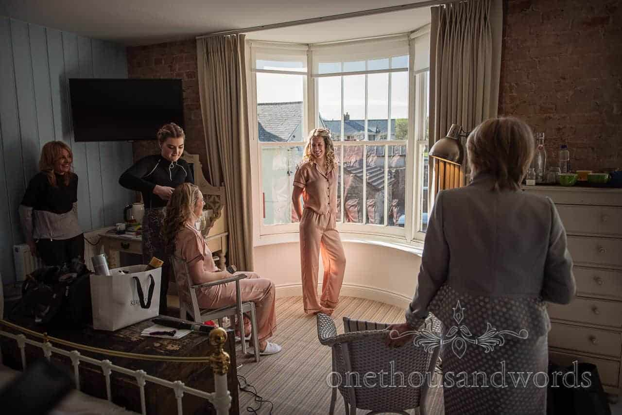 Bridesmaid in peach bride squad pajamas stands in bay window on wedding morning