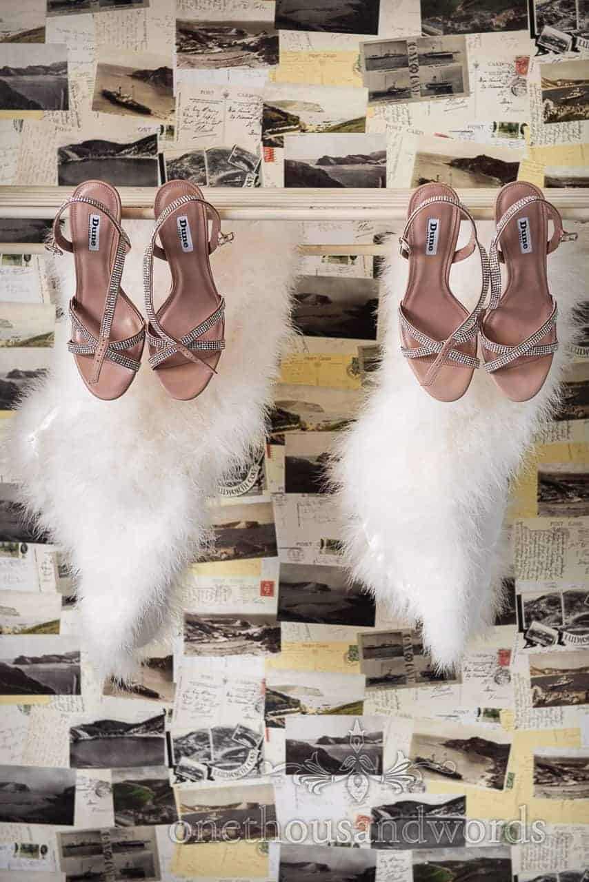 Bridesmaids wedding shoes and feather shawl hang against postcard wallpaper