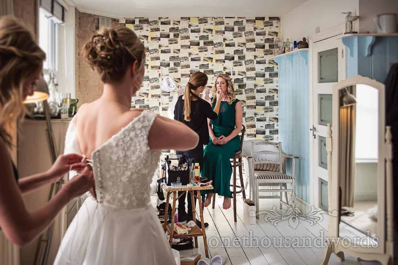 Bridesmaid in green has hair styled while other helps bride with dress