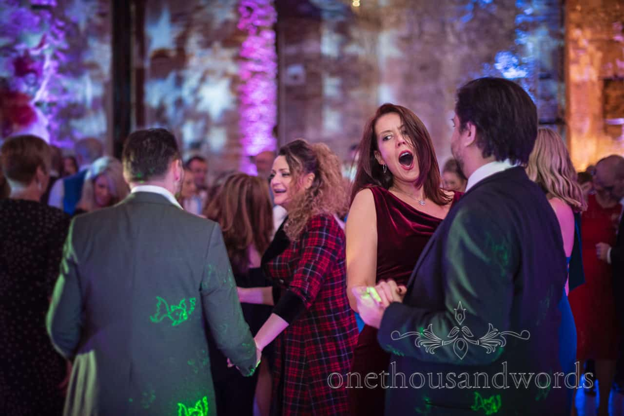 Singing and dancing guests on busy dance floor with disco lighting and lazers