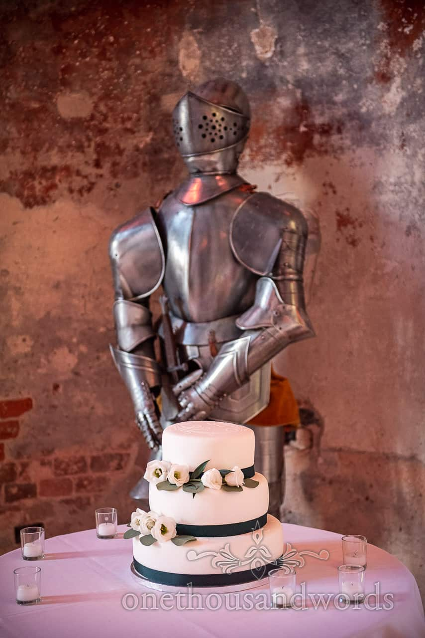 Three tier cake is guarded by suit of armour Lulworth Castle wedding