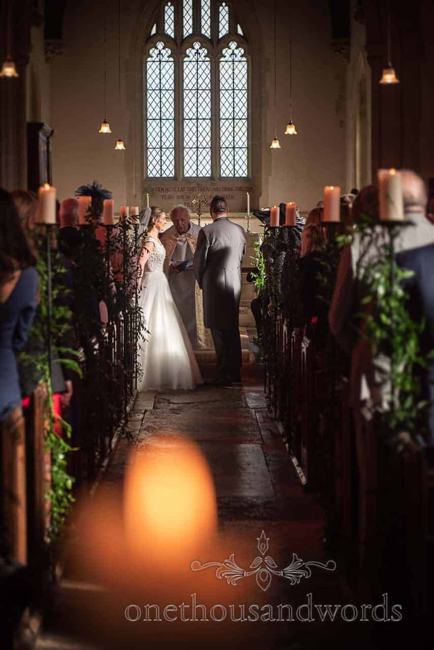 Bride and groom during church ceremony at Lulworth Estate wedding
