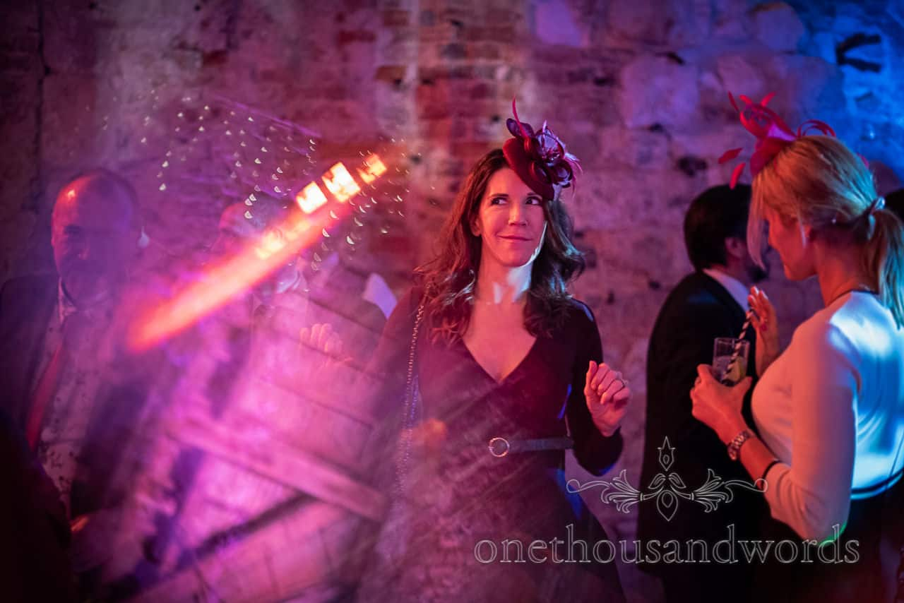 Dancing guests in stage lighting at Lulworth Castle wedding reception