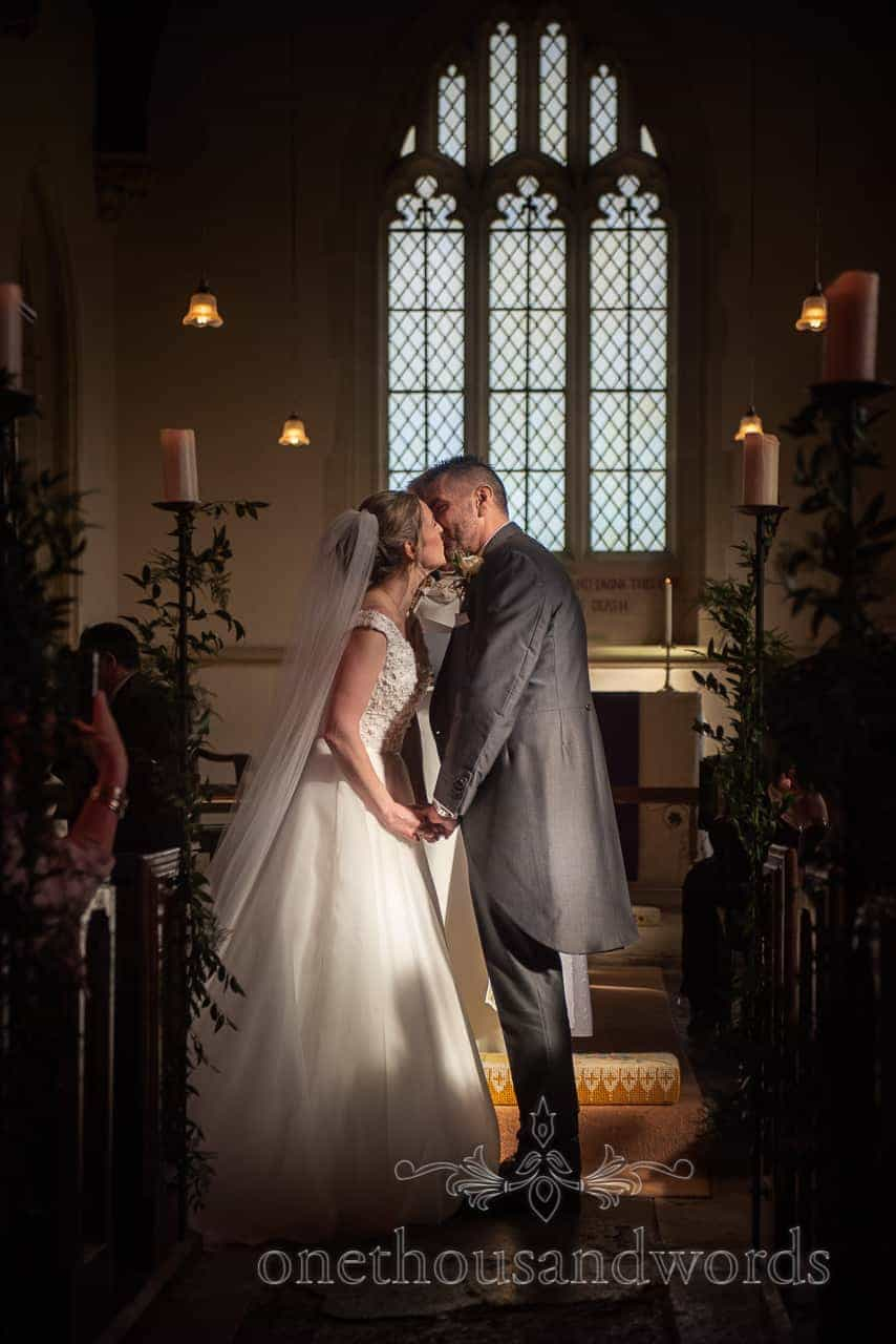Newleywed first kiss at Lulworth Estate church wedding photographs