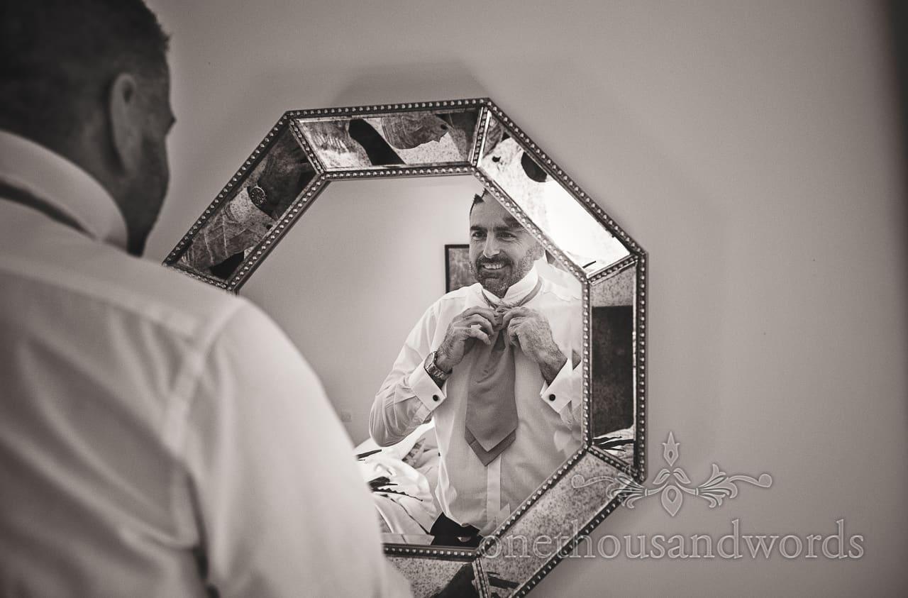 Smiling groom adjusts cravat in mirror on Lulworth Estate wedding morning